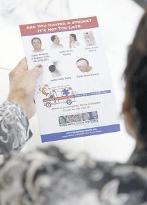 A senior reads over a refrigerator magnet with information on the signs of having a stroke and what steps they should take to minimize damage. (AP photo)
