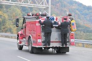 LAST RIDE — The flag-draped casket of Jenkins Volunteer Fire Department member Mark Joseph Sturgill rode atop a Jenkins fire engine on the way across Pine Mountain to Sturgill's final resting place in neighboring Virginia. Sturgill was honored with a firefighter's funeral on Oct. 13 for his years of service to his community. The 48-yearold volunteer fireman was gunned down in front of his home earlier this month. Samuel Todd Collier, 32, has been held without bond since he was arrested October 8 and charged with murdering Sturgill. The case awaits action by the Letcher County Grand Jury. (Photo by Chris Anderson)