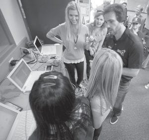 Jimmie Johnson, four-time defending NASCAR Sprint Cup Series champion, and his wife, Chandra, left, listened to students explain their science projects in a laboratory at Emerald Middle School in his hometown of El Cajon, Calif., earlier this month. The laboratory was built with part of the $100,000 Johnson's foundation gave the school. (AP Photo)