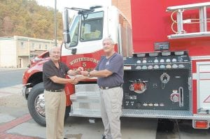 SHINY NEW TRUCK — Whitesburg Mayor James Wiley Craft (left) handed Whitesburg Fire Chief Gary Mullins the keys to a brand new 2011 pumper tanker, which can hold 2,000 gallons of water. The fire truck was purchased through a $100,000 Rural Development grant obtained with the help of the Letcher Fiscal Court and a $144,000 loan through the Kentucky League of Cities.