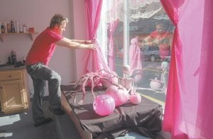 """SPOOKY IN PINK — Keith Adams, owner of The Looking Glass Hair Salon, put the final touches on a pink Halloween window display for the """"Wipe out Whitesburg with Pink"""" contest sponsored by the Zeta Zeta, Chapter of Beta Sigma Phi Sorority of Letcher County in observance of National Breast Cancer Awareness Month."""