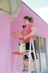 PAINTING IT PINK — Pictured above Jane Adams, an employee of Annie's Frugal Finery in Whitesburg, painted the store front pink on Oct. 18. Shown below are the front windows of Hobo's Diner which raise awareness of the importance of early breast cancer detection to increase chances of survival. In observance of Breast Cancer Awareness Month, Zeta Zeta, Chapter of Beta Sigma Phi Sorority of Letcher County is encouraging local businesses, organizations, churches and schools to
