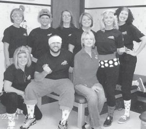 EXERCISING FOR A CURE — Staff members of East Kentucky Physical Therapy and Sports Clinic wore pink in an '80s theme on Oct. 22 to promote a cure for breast cancer. Pictured are (left to right, back) Miranda Dixon, Trina Stanley, Millie Hampton, Stacey Banks, Melissa Griffith, (front) Allie Dixon, Matt Craft, Debbie Cook and daughter Brandy Baker. Debbie Cook is a breast cancer survivor.