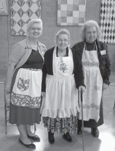 VINTAGE APRONS — Three sisters, Betty Eldridge, Virginia Caudill and Nona Roark, modeled their vintage aprons which have a special meaning to their family. They are members of the Letcher Area Homemakers Club, which had 19 club members and guests attending the area meeting.