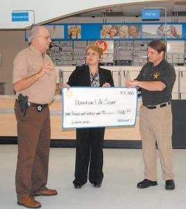 Whitesburg Walmart Manager Earline Delph (center) presented Letcher County Sheriff Danny Webb (left) and Deputy Eugene Slone with a check for $1,000 to benefit the Operation LifeSaver program, which is aimed at helping locate people diagnosed with dementia and other disorders if they ever wander from home. Delph presented several checks to local organizations as a part of the re-grand opening celebration on Nov. 5.