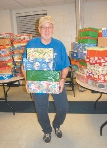 Randy Craft carried several gift-filled shoeboxes at Whitesburg First Baptist Church on Nov. 15. The boxes will be delivered to less fortunate children in at least 100 diff erent countries including the United States as part of Operation Christmas Child. Whitesburg First Baptist Church serves as a collection center for southeast Kentucky/southwest Virginia. Last year the Whitesburg church collected 11,727 shoeboxes. The gift-filled shoeboxes can be dropped off at the church from 5 until 8 p.m. Wednesday (today) through Friday, 10 a.m. until 6 p.m. on Saturday, 12 until 6 p.m. on Sunday, and from 3 until 8 p.m. on Monday. Nov. 22 is the last day to take shoeboxes to the church.