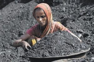 An Indian woman laborer works at a coal warehouse in Gauhati, India. State-run Coal India is in talks to acquire Peabody Energy Co. and Massey Energy Co. (AP Photo)