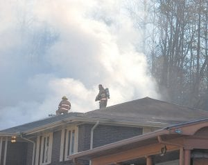 """Firefighters with the Whitesburg Fire Department worked Monday morning to extinguish flames at the West Whitesburg home of Dr. Byron Thomas and his wife Amanda. The cause of the fire hasn't yet been determined. """"It happened during an eight-minute period,"""" said Dr. Thomas. """"It just happened really fast."""" (Photo by Sally Barto)"""