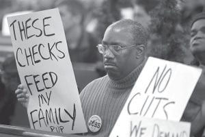 """Frank Wallace, who is unemployed, displayed a sign during a """"Vigil for the Unemployed"""" at the Arch Street Methodist Church in Philadelphia last week. The number of people applying for unemployment benefits fell sharply last week to the lowest level since July 2008, a hopeful sign that improvement in the job market is accelerating.(AP Photo)"""