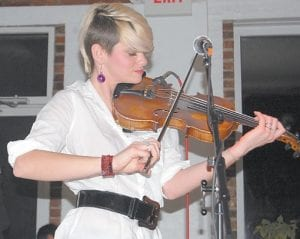 FIT FOR FAMILIES — For two weekends in a row, audiences at Summit City in Whitesburg were treated to music played by bands entirely or partially composed of siblings. In photo at top, Scarlett Rische of Nashville based Jypsi played the fiddle for a large audience who attended their country music show on Dec. 4. Pictured below are brothers James Wilson (left) and Sam Wilson of Charlottesville, Va.-based Sons of Bill, which impressed a nearly full house with their brand of rock the week before. (Top photo by Sally Barto. Bottom photos by Joann Harvey)