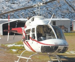 """UNLIKELY LANDING PAD — This helicopter was surveying power transmission lines for a coal company when it ran into a """"static wire,"""" broke its windshield, and was forced into an emergency landing near Isom. The helicopter's pilot suff ered a cut to his face. Two passengers escaped injury. See story, Page 13. (Photo by Sally Barto)"""