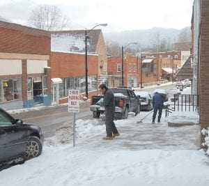 OBEYING CITY LAW — Billy Brown poured salt while Josh Combs swept snow from a sidewalk Tuesday morning in front of Western Auto on Main Street in Whitesburg. A city ordinance requires business owners and residents to keep sidewalks and steps to their buildings clear of ice, snow and other obstructions. (Photo by Sally Barto)