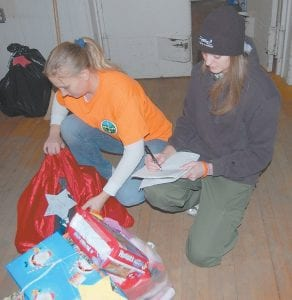 Sisters Tiff anie Combs and Tara Combs (far right) organized gifts on Dec. 10 at the Letcher County Tourism Building. This is the first year that Pine Mountain Search and Rescue has had charge of the program, which provides gifts to needy children. Organizers say 325 children will receive gifts from the program this December.