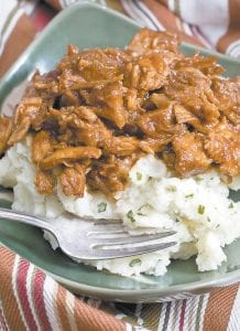This photo shows a stovetop-created cider-barbecue pulled pork over mashed potatoes. This pulled pork recipe, which appears on this page at left, is very simple yet filling meal. (AP Photo/Larry Crowe)
