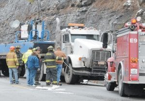Rescue workers tend to a tractor-trailer involved in Saturday's accident at Kona. (Photo by Chris Anderson)
