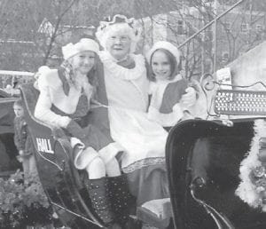 PARADE — (Left to right) Molly Collins, Mrs. Claus and Mackenzie Cook rode in a carriage in the Whitesburg Christmas Parade. Molly is the daughter of Jamie and John Collins, and Mackenzie is the daughter of Regina and Richard Cook. Both are members of the Silver Spinners.