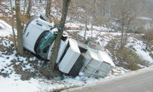 "Letcher County Sanitation Dept. driver Larry Sturgill escaped injury when this ""mini-packer"" slid on an icy driveway and rolled down a hill beside KY 7 near Deane. The accident is expected to lead Letcher County Judge/Executive Jim Ward to ask the Letcher Fiscal Court for changes in the way the county's garbage is collected."