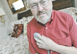 Rik Krohn displayed the remote control unit he uses to turn on an experimental nerve stimulator to combat his sleep apnea at his home in Burnsville, Minn. (AP Photo)