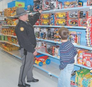 "Above, Kentucky State Police Trooper Jody Sims helped a boy pick out a remote control motorcycle during the KSP ""Shop with a Trooper"" event at the Whitesburg Walmart on Jan. 6."