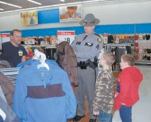 "At right, Kentucky State Police Sgt. Barry Engle checked the size of a coat during the KSP ""Shop with a Trooper"" event. The shopping trip was postponed from before Christmas until last week because of inclement weather. At least 86 children from Letcher, Knott, Leslie, Perry and Breathitt counties were able to pick out items totaling around $125 each."