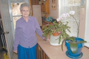 """Evelyn Kincer, 87, of Pine Creek, has enjoyed the blooms of her Christmas cactus and orchid. Kincer has placed six ice cubes in the flowerpot with the orchid two times a week since October and has continued to trim back the cactus. """"This has been so beautiful,"""" said Kincer."""