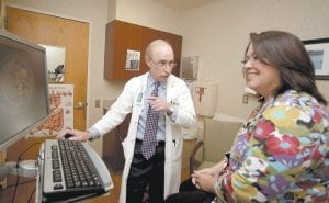 Dr. Paul J. Pockros, head, Division of Gastroenterology/ Hepatology and director, Liver Disease Center, talked with patient Loretta Roberts as they viewed her information on a computer screen in his exam room in San Diego. (AP Photo)