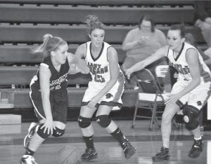 Letcher County Central Lady Cougars Haley Whitaker and Erica Meade teamed up to defend the Knott Central offense in the Lady Cougars' win over the Lady Patriots, 49-46, on Sunday. The Lady Cougars followed up the district win with another on Monday, defeating June Buchanan, 79-33, to improve to 12-8 on the season and 8-2 in the district. (Photo by Chris Anderson)