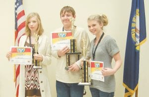 Dalton Seals (pictured at center), an eighth-grade student at Letcher Elementary School, won the Letcher County Public School District spelling bee held at the school bus garage on Feb. 4. Ashley Benton (right), a seventh-grade student at Whitesburg Middle School, placed second. Alexis Lewis, a seventh-grade student at Arlie Boggs Elementary School, placed third. Seals, 14, correctly spelled corporal to win the district-wide competition. He will represent the district March 9 at the Kentucky Derby Spelling Bee at the PNC Club at Papa John's Cardinal Stadium in Louisville.
