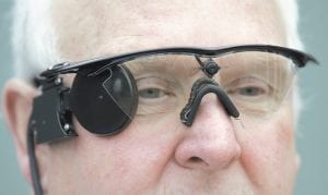 """Eric Selby posed for a photograph Saturday with a """"sight"""" camera fitted in a pair of glasses, which works in conjunction with an artificial retina implant called the Argus II fitted in his right eye, enabling him to detect light, in Coventry, England. For two decades, Selby, 68, had been completely blind and dependent on a guide dog to get around. But after having an artificial retina put into his right eye, he can detect ordinary things like the curb and pavement when he's walking outside. (AP Photo/Martin Cleaver)"""