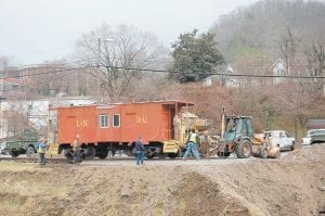 Tri-State Rail Services workers laid railroad tracks to move a caboose parked near the Letcher County Veterans Memorial Museum in downtown Whitesburg Tuesday. A 30-foot expansion will be added to the museum. Wayne Collins, foreman of the Sapphire Coal Company prep plant at Thornton, rode aboard the caboose and controlled the brake. The rail services and coal companies donated materials and labor for the move.