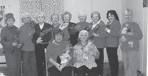 Roses were given to the ladies at the Ermine Senior Citizens Center on Valentine's Day. (Left to right, standing) Helen Bentley received roses from her son Randy, Yvonne Hammock from her husband Lennon, Pauline Adams from her husband Richard, Coleene Hart from her husband Rhuford, Betty Pike from her husband Ed, Doris Bentley from her husband Joe, Shirley Day from her husband Charles, (seated) Site Manager Debbie Slone from her husband, and Lizzie M. Wright from a secret admirer. She asks, 'Who is he?'