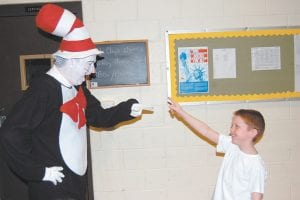 """THE 'CAT' VISITS — Acting as The Cat in the Hat, Keith Adams joked with Landon Tolliver, a first grader at West Whitesburg Elementary School, on March 3. Adams recited """"The Cat in the Hat"""" book by Dr. Seuss at three elementary schools last week in celebration of Read Across America week and Dr. Seuss's birthday."""