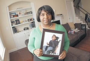 Beatrice Diaz holds a photograph of her son Garrison, 8, at her home in Chapel Hill, N.C. Diaz unexpectedly went into labor at 24 weeks while pregnant with Garrison, who after delivery was so fragile she was not even allowed to hold him for a month. Today he is in a wheelchair and has the mental capacity of a 9-month old. (AP Photo/Jim R. Bounds)