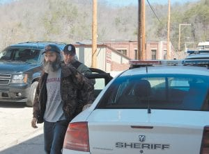 Billy Hubbs, of Partridge, was taken to the Letcher County Jail after being arrested on a drug-related charge Tuesday afternoon. He is being escorted by Lt. Brian Damron of the Letcher County Sheriff 's Department. Hubbs is one of 21 Letcher County residents charged in a drug investigation organized by Operation UNITE.