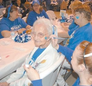 Ethel Banks, 94, of Cowan smiled as Amber Trent, an employee with the Letcher County Senior Citizens program, painted a blue paw print on her cheek. Senior citizens from all over the county attended a March Madness party at the Kingscreek Center on March 15 to show their support for the University of Kentucky Wildcats men's basketball team, which will play Princeton in the first round of the NCAA tournament on Thursday.
