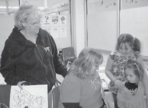 Gertrude Tyree, Stevie Cook, and Jadia MacRoy looked at Grayson Holbrook's Plate Head books during Literacy Night at West Whitesburg Elementary School.
