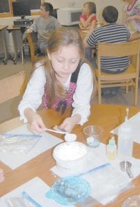 """Marissa Maggard, a fourth-grade student at Letcher Elementary School, measures a tablespoon of cornstarch in the school library. Students made rubber """"bouncy balls"""" out of corn by-products from directions provided by the Kentucky Department of Agriculture's mobile science center. Directions listed on B1 of this week's Mountain Eagle detailing how to make a bouncy ball mistakenly left out step eight, which is to take out your newly formed sheet of plastic out of the resealable bag and form into a ball. The bouncy ball must harden for at least 10 hours for best bouncing results. (Photo by Sally Barto)"""