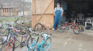 Mick Polly, of 48 5th Street, Whitesburg, stands near old bicycles he plans on refurbishing for Letcher County children to ride. Polly is seeking old bikes and parts.