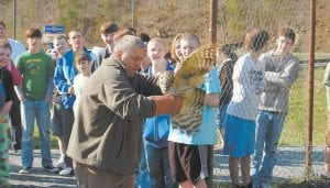 "Students at Cowan Elementary caught a glimpse of a barred owl before Master Falconer Mitch Whitaker, of Roxana, released the bird back into the wild at Cowan on March 17. The barred owl was hit by a car about three weeks ago at Millstone. Whitaker has been caring for the animal through the Letcher County 4-H raptor rehabilitation program in Whitesburg. ""Hopefully it will fly and survive like it is supposed to,"" Whitaker said. (Eagle photo)"