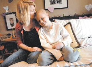 Peyton Armstrong, 10, sits at home with his mother, Jessica Armstrong, in Glenwood Springs, Colo. Peyton, who is battling leukemia, received national attention after contracting a severe infection from using medical alcohol wipes. (AP Photo/Glenwood Springs Post Independent)