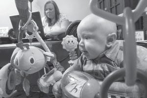 Five-month-old Oliver Michael DiCicco played while his mother Sheri Lee Schearer, 34, worked nearby at a computer last week in Pennsville, N.J. Schearer says a study that found mothers of young children were heavier and ate more calories, sugary drinks and fatty foods than childless women, reflects her life. Before, she had time to make a spinach salad, or go out for one. Now, she grabs whatever is easiest and quickest. (AP Photo)