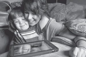 Grady Oathout, 3, embraces his mom Tara Oathout, as they play together on an iPad. Tara says her son, who has autism, was trapped in a world to himself, unable to communicate his desires to his parents. Oathout says with the use of the iPad, Grady can tell them what he wants and how it feels. Tara has founded a group called Loud Mommy Ministries to get iPads into the hands of other parents with autistic children. (AP Photo/Peoria Journal Star)