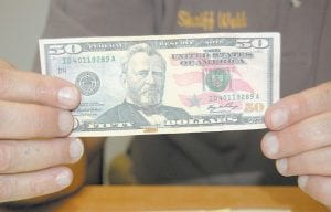 Letcher County Sheriff Danny Webb held a counterfeit $50 bill found at the Ermine Double Kwik Monday. Webb is advising people to pay close attention when exchanging money.