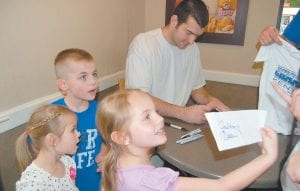 — Tori Holcomb, 7, of Whitesburg, showed her mother, Marsha Holcomb, the autograph she got from Josh Harrellson. The graduating senior basketball center drew a heart beside his name for Tori during a visit to Wendy's restaurant Tuesday night. Also pictured are Tori's sister, Kara, 4, and brother, Luke, 8. More coverage appears inside on Page 9. (Photo by Sally Barto)