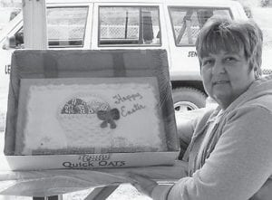 EASTER CAKE — Ermine Senior Citizens Center Site Manager Debbie Slone holds an Easter cake furnished by Community Trust Bank in Whitesburg for the senior Easter picnic.