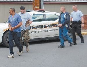 Tommy Hutton, left, and J.J. Wright, third from left, were escorted to the Letcher County Sheriff 's Department by Lt. Brian Damron and Officer Tim Miller of the Neon Police Department. Hutton and Wright were arrested last week on drug trafficking charges and remain lodged in the Letcher County Jail.