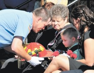 A Neon volunteer firefighter presents Mike Webb's fireman's helmet to Webb's son, Cameron Michael Webb, during a memorial ceremony Saturday at Millstone. Hundreds turned out to honor Webb, a longtime firefighter and teacher, after Webb died April 27 at his Goose Creek home, shortly after returning from an emergency call. He was a member of the Neon Volunteer Fire Department for 27 years and a teacher and bus driver at Fleming Neon Elementary School. He is survived by his wife, Debbie; two daughters, Tamara Brooke and Brittany Nicole; and son Cameron Michael. (Photos by Chris Anderson)