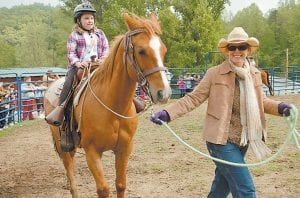 Makenzie Holmes is one of about 50 second-grade students at Letcher Elementary who rode horses at Revelation Ranch in Blackey on May 5 during a class field trip. Peri Pardo guided the horse. (Eagle photo)