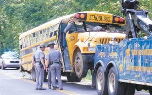 Kentucky State Police troopers gathered around a Carlisle County school bus that crashed Monday near the community of Cunningham, Ky. One child was killed in the crash, while several of the 29 children on board the bus were injured and taken to western Kentucky hospitals. (AP Photo/The Paducah Sun, Will Pinkston)
