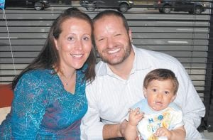 A family photo shows Dianna Fiore Radoslovich of New York, with her husband Steve and son Steven Andrew, celebrating his first birthday. Radoslovich's multiple sclerosis symptoms — including difficulty walking — temporarily disappeared with her first pregnancy, but her second pregnancy hasn't brought the same reprieve. Pregnancy adds a new challenge for women with physical disabilities. (AP Photo)